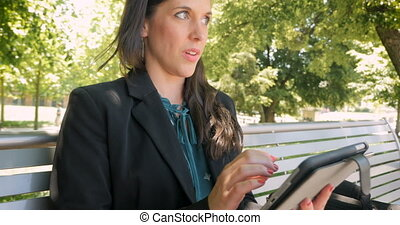 Attractive woman remembering something and smiling while on digital tablet