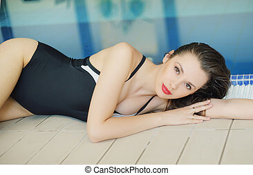 Attractive woman resting by the pool