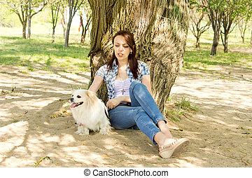 Attractive woman resting in shade with her dog