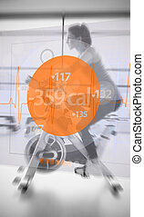Attractive woman riding exercise bike with futuristic...