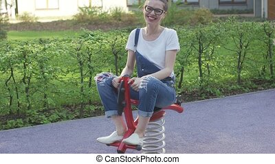 Attractive woman riding spring toy on playground