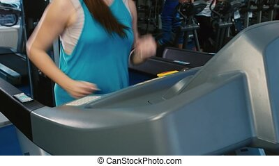 Attractive woman running on a treadmill, smiling. Training at the gym