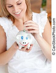 Attractive woman saving money in a piggy-bank