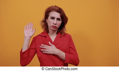 Attractive caucasian young woman showing palm at camera, keeping hand on chest, looking directly wearing fashion red jacket over isolated orange background. People lifestyle concept.