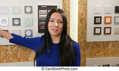 Attractive woman shows and tells about the light switches in different colors and shapes. Samples are presented back to the stand. Black long hair and a blue dress.