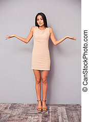 Attractive woman shrugging shoulders