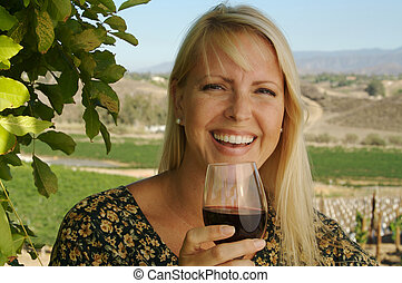 Attractive Woman Sips Wine at a Winery in the country.