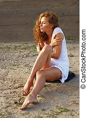 Attractive woman sits on sand