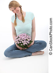 Attractive woman sitting and holding flowers