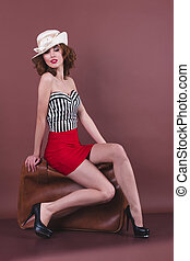 Attractive woman sitting on a retro suitcase