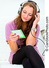 Attractive woman sitting on couch at home and listening music in headphones