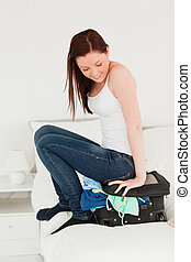 Attractive woman sitting on her suitcase