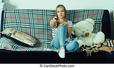 Attractive woman sitting on the couch and watching TV