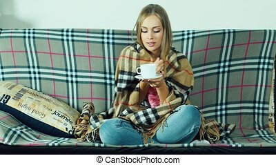 Attractive woman sitting on the couch: it is very cold