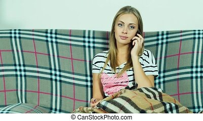 Attractive woman sitting on the couch and talking on a cell phone, smiling