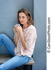 Attractive woman sitting with cup of coffee