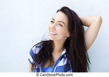 Attractive woman smiling against a wall