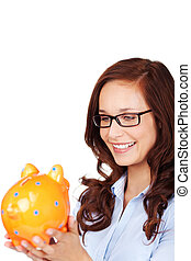 Attractive woman smiling at a piggy bank