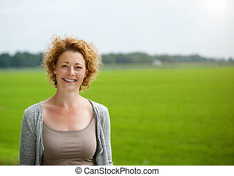 Attractive woman smiling outdoors by green countryside