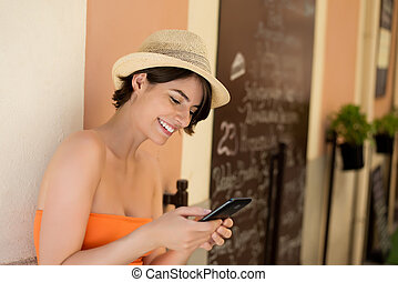 Attractive woman smiling while writing a message