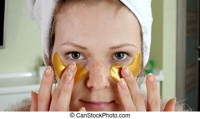 attractive woman spplying cosmetic facial patches at home 4k