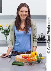 Attractive woman standing in her kitchen