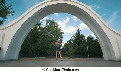 Attractive woman stands under the arch playing violin in...