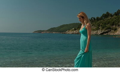 Attractive woman strolls along coast on sunny day outdoors.