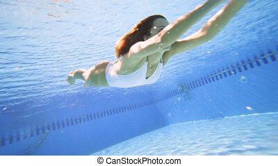 Attractive woman swimming in pool in slow motion