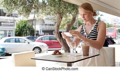Attractive woman taking picture of a pastry on her mobile