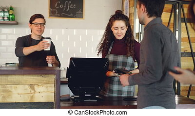 Attractive woman talkative cashier is accepting contactless...