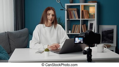 Attractive woman talking on video camera at home