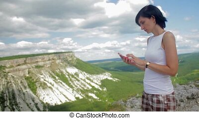 Attractive woman texting on smartphone on a background of mountains