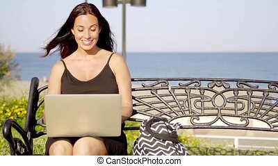 Attractive woman typing on her laptop outdoors