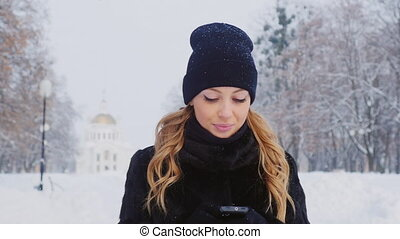 Attractive woman uses a smartphone, is in the winter park