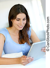 Attractive woman using digital tablet at home