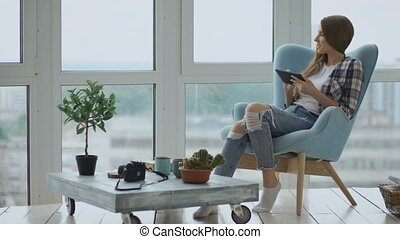 Attractive woman using digital tablet sitting in chair at balcony in loft modern apartment