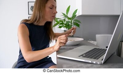 Attractive woman using her laptop while having a breakfast