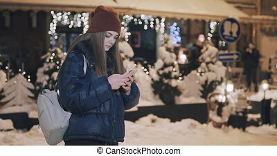Attractive Woman using Mobile Phone on Streets of Night Town