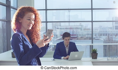 Attractive woman using smart phone in the office.