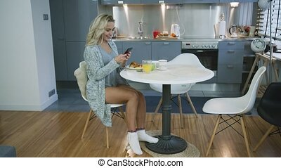 Attractive woman using smartphone during breakfast -...