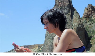 Attractive woman using smartphone on the beach.