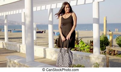 Attractive woman waiting on a seafront promenade -...