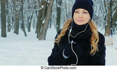 Attractive woman walking in a winter park, listening to music on headphones
