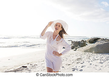 Attractive woman walking on beach with hat