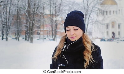 attractive woman walking on the street in the winter and listening to music