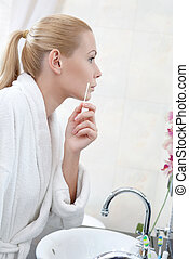 Attractive woman washes face with lotion
