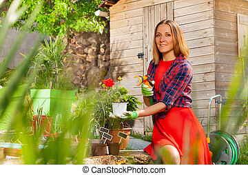 Attractive woman watering plants in the garden