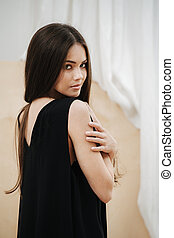 Attractive woman wearing a black V-neck dress looking over her shoulder