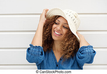 Attractive woman wearing hat and smiling on white background